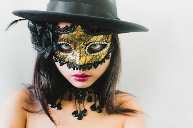Femme avec un masque vénitien d'or et un chapeau noir sur un fond blanc