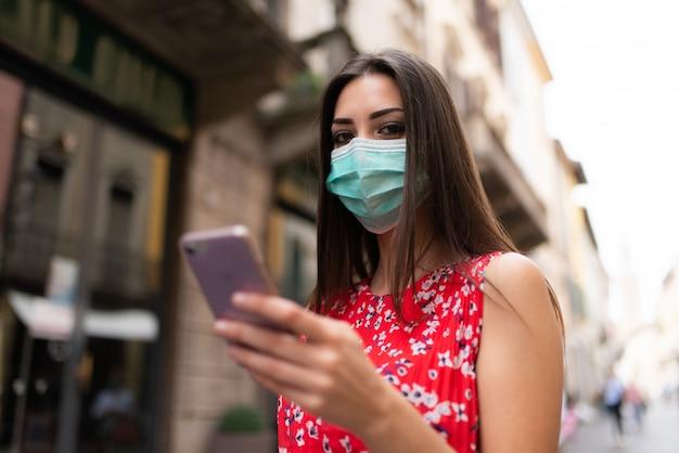 Femme masquée marchant dans une ville tout en utilisant son téléphone portable