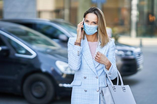 Une femme masquée parle sur un téléphone portable. photo de haute qualité
