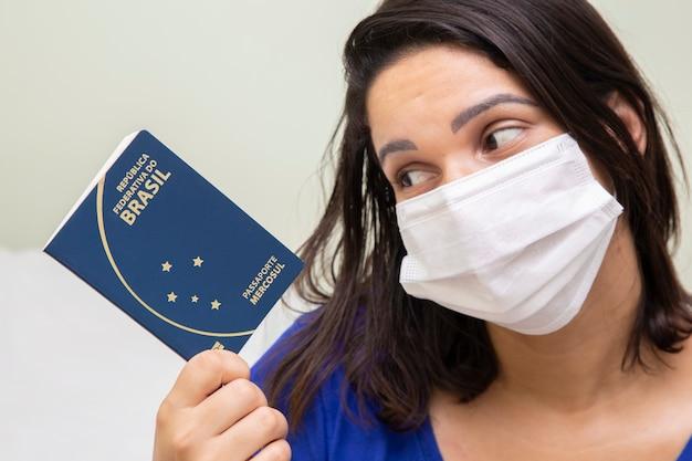 Femme masquée avec passeport brésilien à la main.