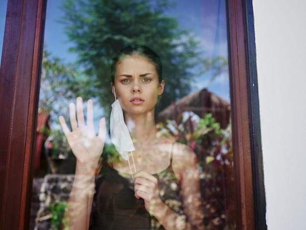 Femme masquée regardant par la fenêtre quarantaine de verrouillage