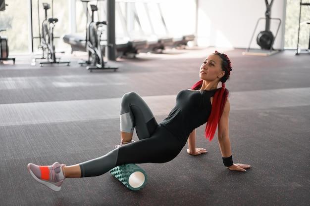 Femme massant le rouleau de mousse gym jambe exercice de libération myofasciale roulant, points de déclenchement