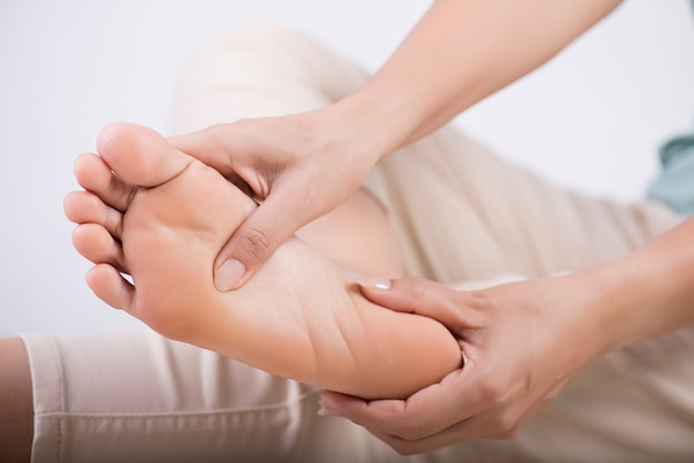 Femme, masser, pied douloureux