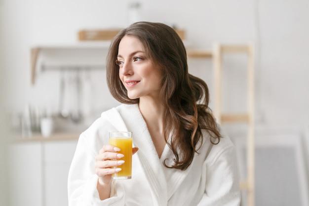 Femme le matin avec du jus d'orange frais à la main. une femme en peignoir blanc buvant du jus d'orange pour le petit-déjeuner portrait féminin parfait positif du matin. prise de vue en studio.