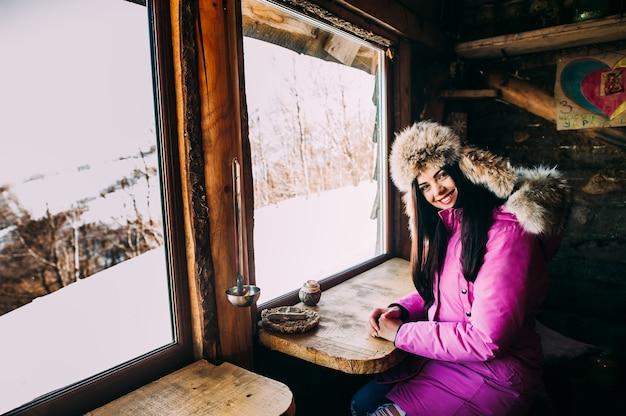 Femme le matin. une jeune femme souriante apprécie le matin ensoleillé dans les montagnes des alpes, en buvant du thé ou du café sur un balcon dans la maison de chalet avec vue sur la montagne.