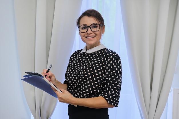 Femme mature d'affaires prospère avec des documents, femme travaillant dans l'hôtel, immobilier, posant