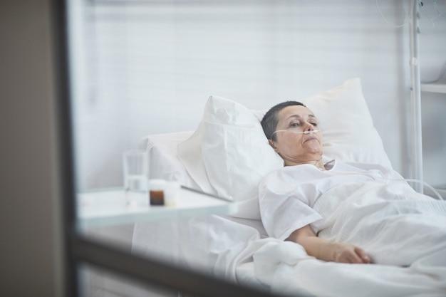 Femme mature allongée sur un lit d'hôpital sous compte-gouttes à l'hôpital
