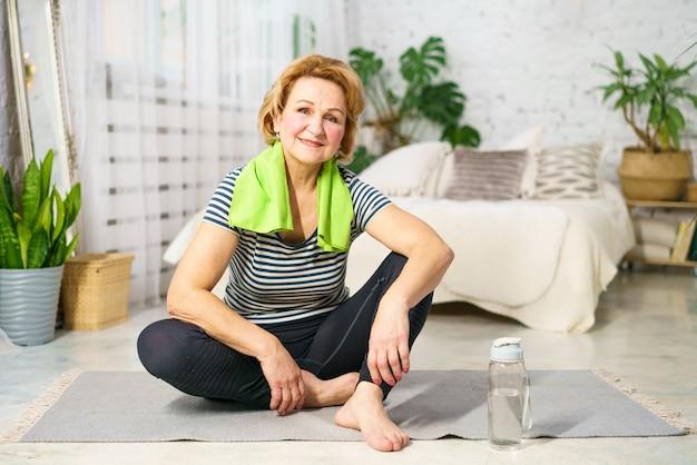 Femme mature après l'exercice se repose assis sur un tapis à la maison dans une pièce avec une serviette autour de son cou équilibre hydrique du corps