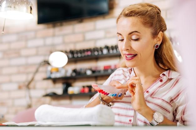 Femme mature attrayante regardant vers le bas et la sélection de la couleur du vernis à ongles