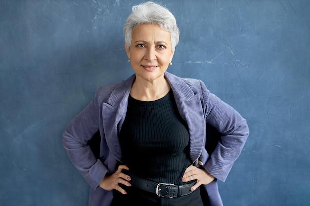 Femme mature aux cheveux gris posant avec veste violette