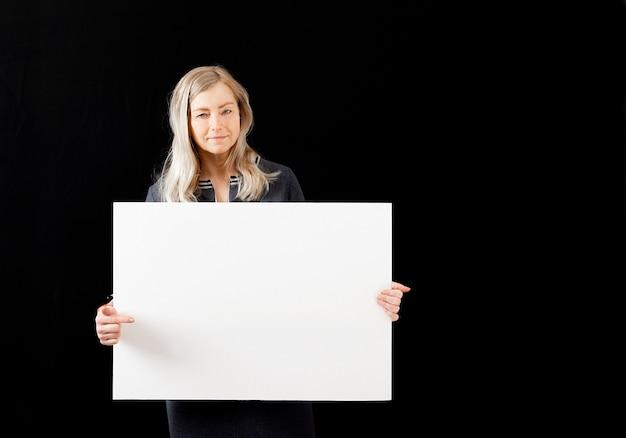 Femme mature blonde d'âge moyen avec une affiche vierge blanche, isolée sur un fond sombre