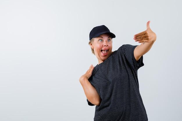 Femme mature blonde dans un t-shirt noir et une casquette noire