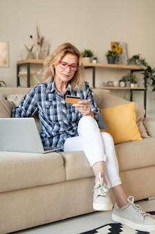 Femme mature blonde regardant la carte de crédit alors qu'il était assis sur le canapé en face de l'ordinateur portable dans le salon et va payer les produits en ligne