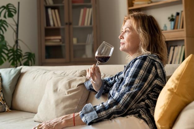 Femme mature blonde avec un verre de vin rouge appuyé contre un oreiller moelleux alors qu'il était assis sur un canapé et profitant d'une journée à la maison