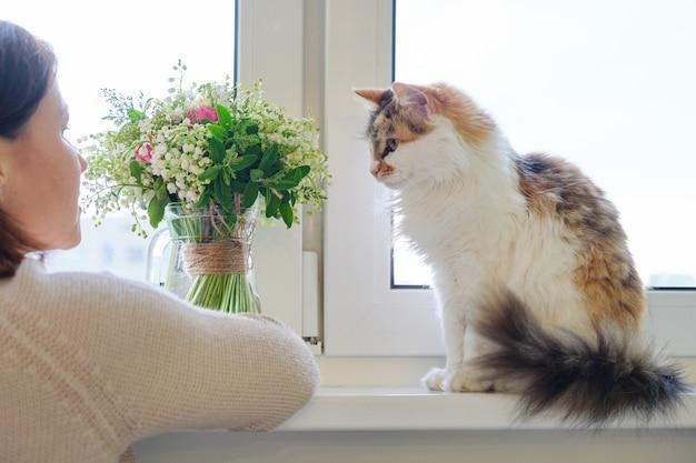 Femme mature et chat tricolore domestique assis sur la fenêtre