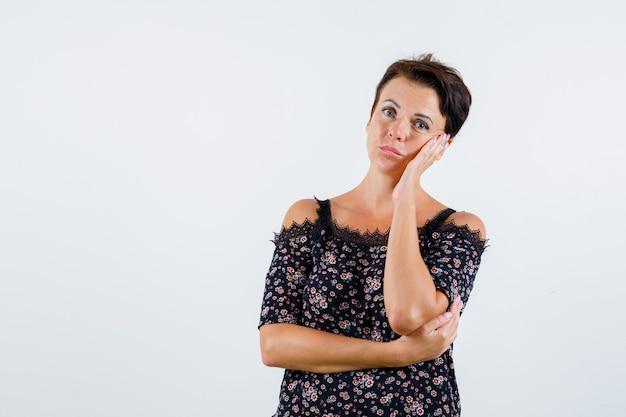 Femme mature en chemisier floral et jupe noire penchée sur la joue sur la paume, pensant à quelque chose et à la vue pensive, avant.