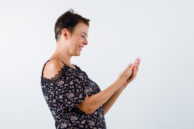 Femme mature en chemisier floral, jupe noire qui s'étend de la main comme tenant quelque chose, souriant et à la joyeuse, vue de face