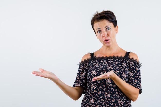 Femme mature en chemisier floral, jupe noire qui s'étend des mains comme tenant quelque chose et à la surprise, vue de face.