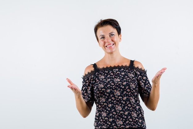 Femme mature en chemisier floral, jupe noire qui s'étend des mains de manière interrogative et à la joyeuse, vue de face.