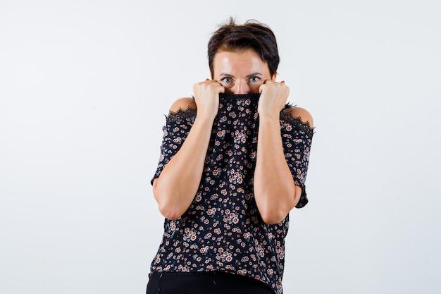 Femme mature en chemisier floral, jupe noire se cachant derrière le col et à la peur, vue de face.