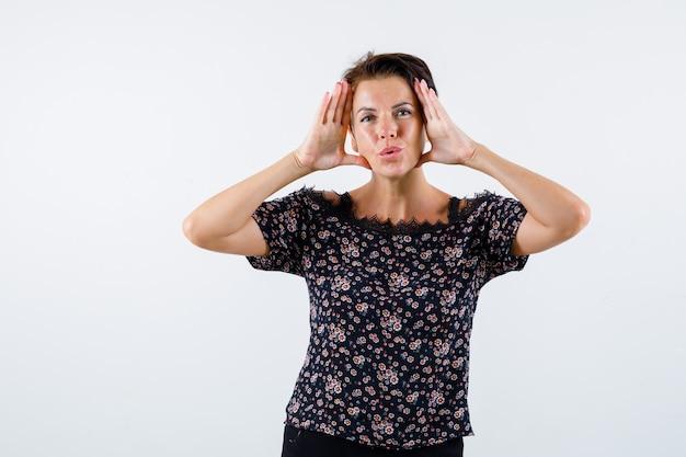 Femme mature en chemisier floral, jupe noire tenant la main pour voir clairement et à la séduisante, vue de face.