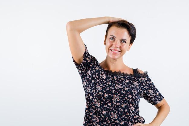 Femme mature en chemisier floral et jupe noire tenant une main sur la tête, une autre main sur la taille et à la vue de face, confiant.