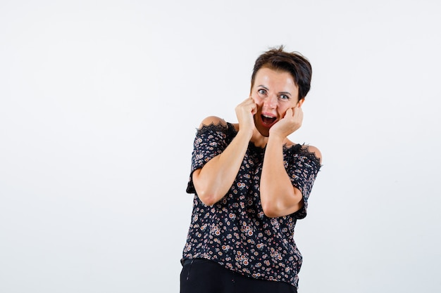 Femme mature en chemisier floral, jupe noire tenant les mains sur les joues, en gardant la bouche ouverte et à la joyeuse, vue de face.