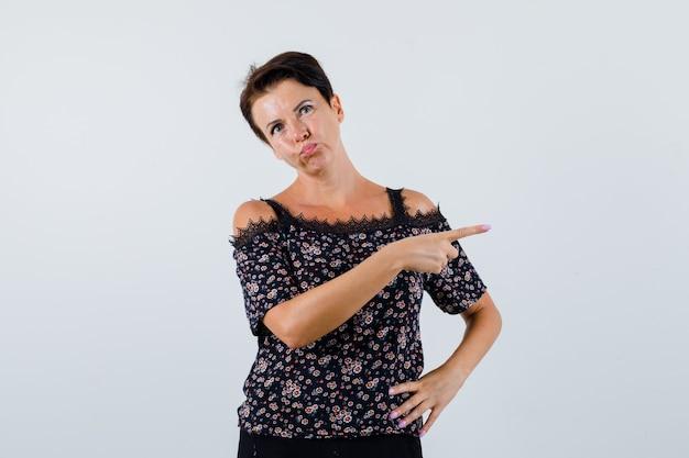 Femme mature en chemisier pointant vers le côté droit et à la vue de face, confiant.