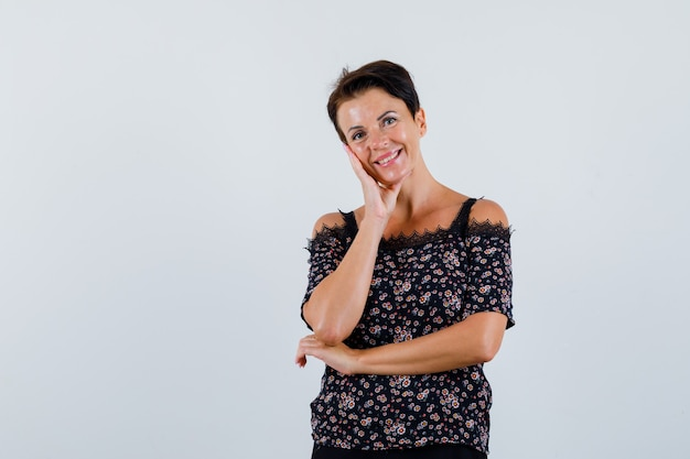 Femme mature en chemisier posant en position debout et à la vue de face, joyeuse.