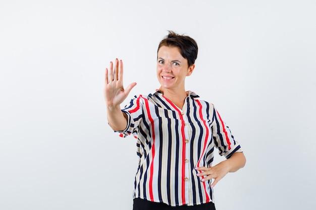 Femme mature en chemisier rayé montrant un panneau d'arrêt, tenant la main sur la taille et à la flottabilité, vue de face.