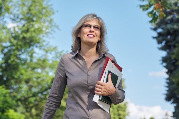 Femme mature confiante d'affaires marchant avec des documents en plein air. belle femme blonde à lunettes, chemise grise, fond de parc de ciel
