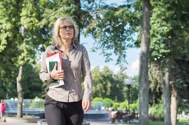 Femme mature confiante d'affaires marchant avec des documents en plein air
