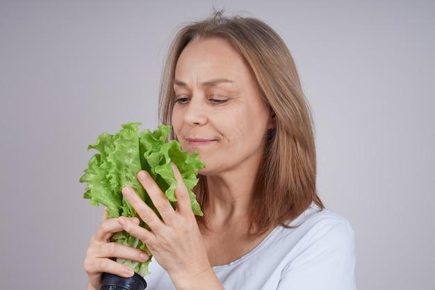 Femme mature dans une chemise blanche tenant un tas de salade verte