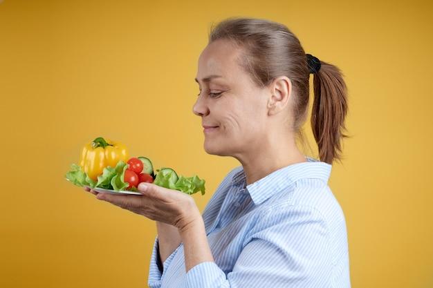 Femme mature dans une chemise blanche tient une assiette de légumes