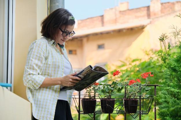 Femme mature debout sur un balcon ouvert en isolement, magazine de lecture féminin seul