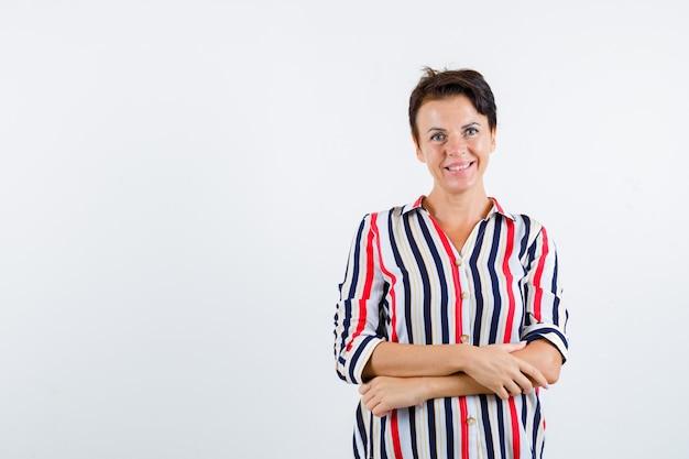 Femme mature debout les bras croisés en chemise rayée et à la recherche de plaisir. vue de face.