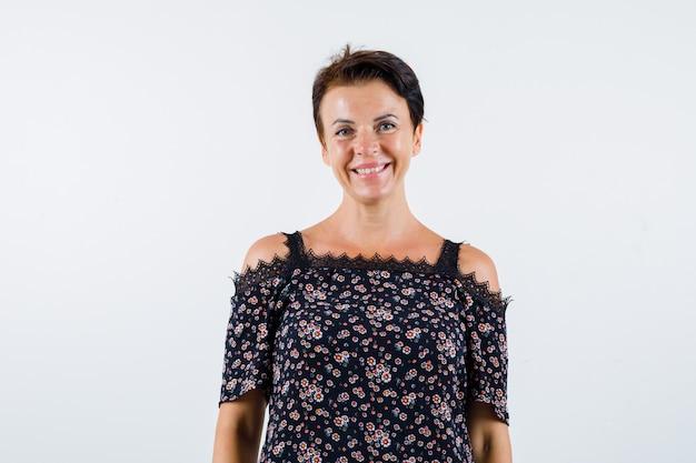 Femme mature debout droite et souriante en chemisier floral, jupe noire et à la confiance. vue de face.