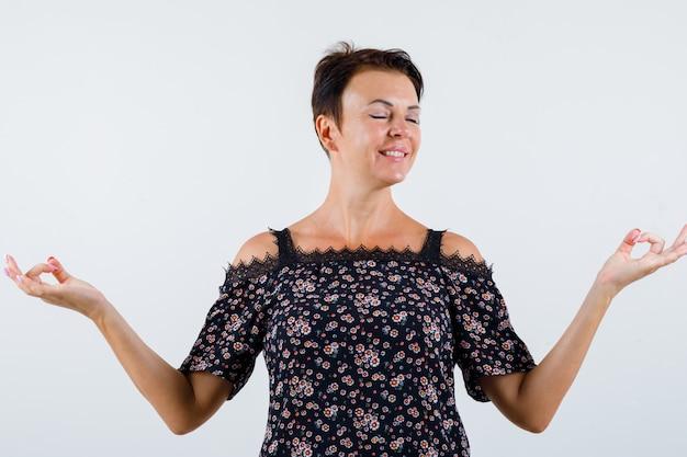 Femme mature debout en méditant pose en chemisier floral, jupe noire et à la vue détendue, de face.