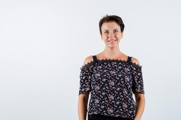 Femme mature debout tout droit et posant à la caméra en chemisier floral, jupe noire et à la joyeuse. vue de face.