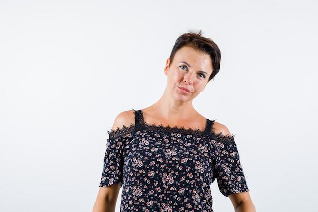 Femme mature debout tout droit et posant à la caméra en chemisier floral, jupe noire et à la vue confiante, de face.