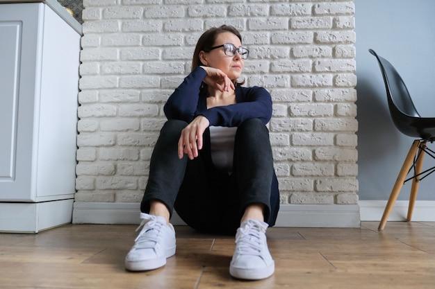 Femme mature déprimée assise sur le sol à la maison