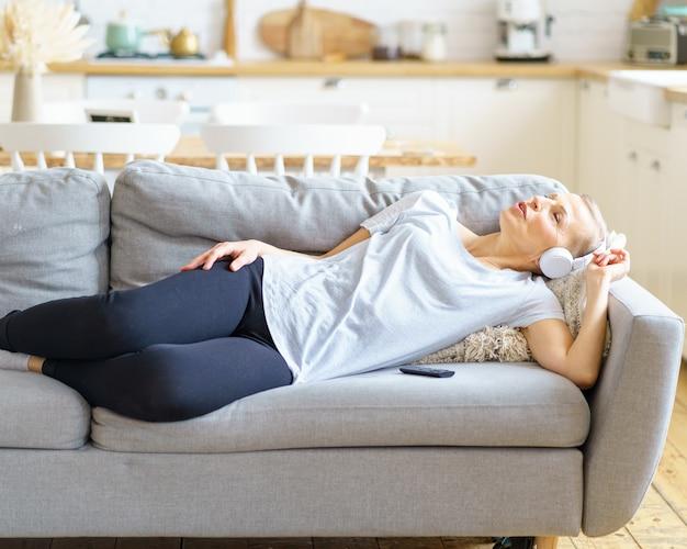 Femme mature écoutant de la musique au casque allongée sur un canapé et rêvant les yeux fermés