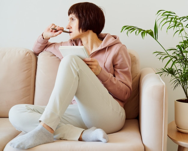 Femme mature écrit sur la liste de todo bloc-notes de la santé mentale journalisation auto-réflexion