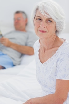 Femme mature inquiète assise dans son lit alors que son mari lit un journal en arrière-plan