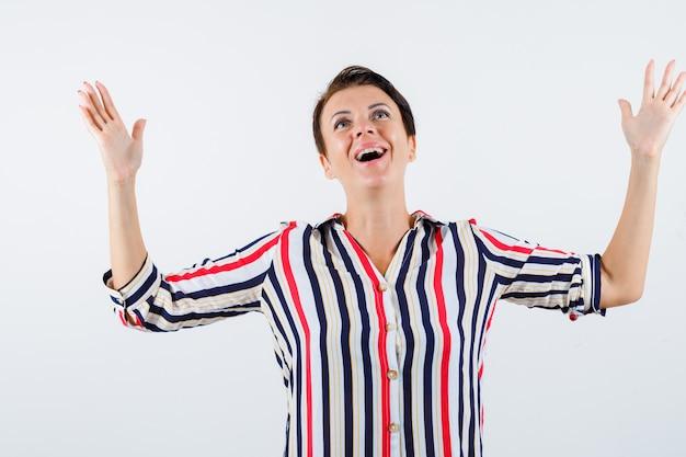 Femme mature levant les mains comme se réjouissant en chemise rayée et à la recherche de plaisir. vue de face.