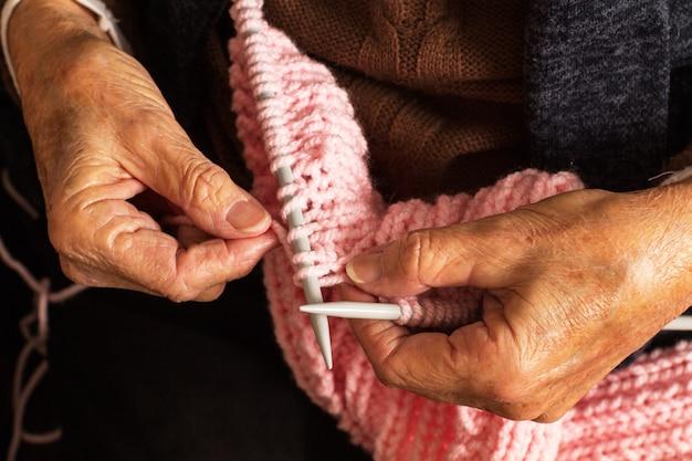 Femme mature mains tricot avec des aiguilles à tricoter et laine rose