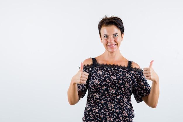 Femme mature montrant deux pouces vers le haut en chemisier à fleurs, jupe noire et à la joyeuse. vue de face.