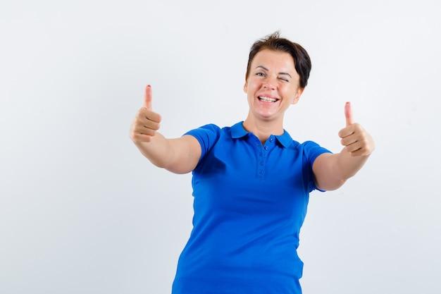 Femme mature montrant deux pouces vers le haut en t-shirt bleu et à la recherche de plaisir. vue de face.