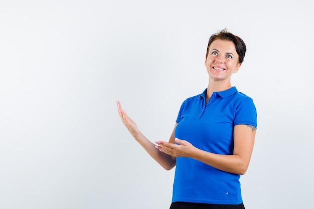 Femme mature montrant un geste de bienvenue en t-shirt bleu et à la vue de face, heureux.