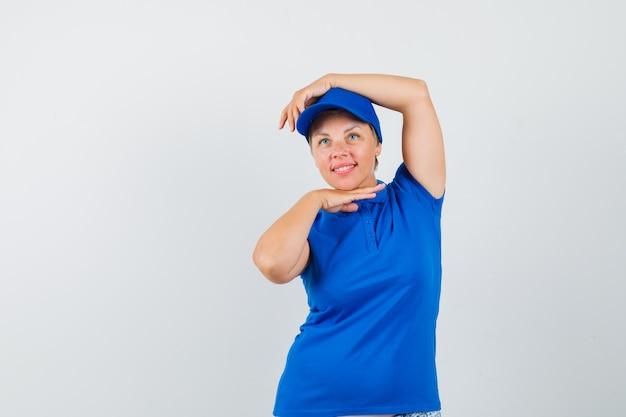 Femme mature montrant le geste de danse en t-shirt bleu et à la mignon.